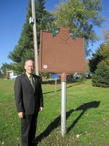 State Representative Doug Green, who represents Utopia, OH (Clermont County), poses by the historical marker that relates the community's beginnings. A photo of Utopia from 1940 is featured on the Society of Ohio Archivists' Archives Month 2014 poster.
