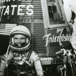John Glenn sitting beside the Friendship 7 spacecraft, 1961
